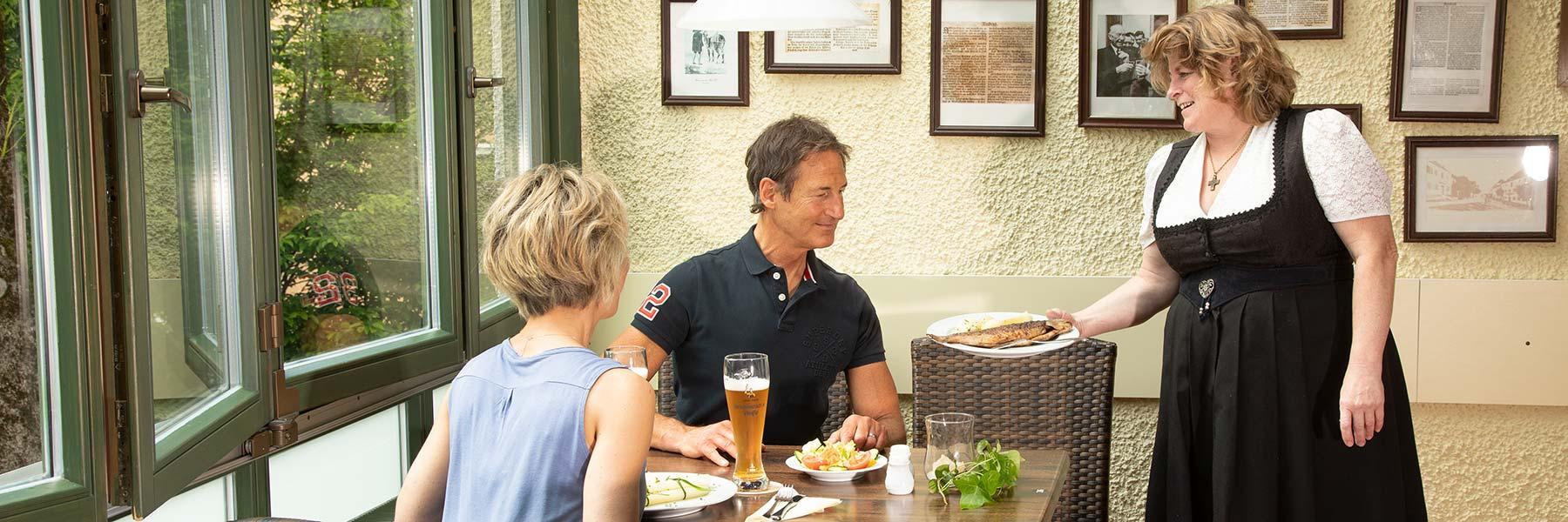 Weißbräu-Wirtin Lisa Putz serviert Gästen ein Fischgericht