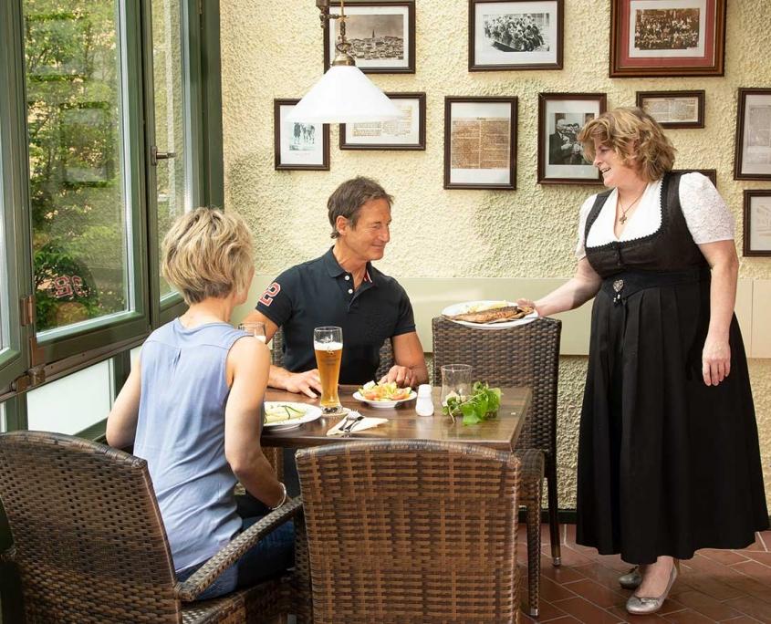 Weißbräu-Wirtin Lisa Putz serviert einen von Küchenmeister Günther Putz zubereiteten Fisch.